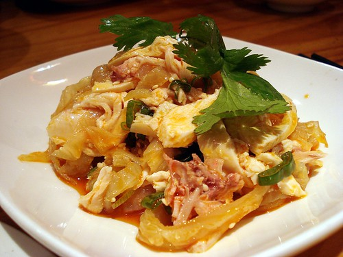 A mixture of shredded jellyfish and chicken pieces is mounded on a white plate, dressed with a sauce based on red chilli oil.  A coriander leaf garnish sits on top.