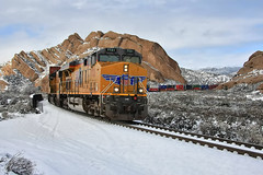 A southbound Union Pacific train through the Snow at Mormon Rocks (Dave Toussaint (www.photographersnature.com)) Tags: california ca travel vacation sky usa cloud snow ice nature up rock train canon landscape photo skies photographer picture stack adobe mojave unionpacific locomotive geology southerncalifornia snowfall cutoff subdivision mormonrocks intermodal 2011 cajonpass 40d topazadjust photographersnaturecom davetoussaint cpcanyon photoshoptopazlabs paldale