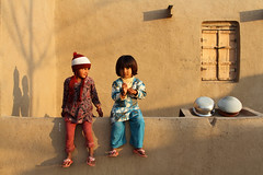 Shadows (Amir Mukhtar Mughal | www.amirmukhtar.com) Tags: girls friends pakistan light portrait window smile wall portraits canon children happy countryside warm sitting colours shadows child shades pots cap amir punjab warmlight villagers villagelife mughal mughals faisalabad mudwall pakistanichildren pakistaniphotos villagelifeofpakistan amirmukhtar wwwamirmukhtarcom villagesofpakistan countrysideofpakistan faisalabad00927
