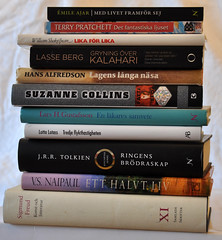 a stack of books including works by VS Naipaul, Suzanne Collins, and JRR Tolkien