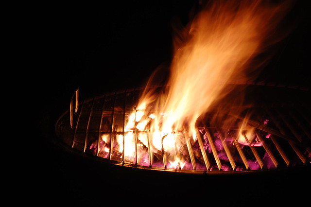 Close up shot of a fire pit, with flames bursting through the cooking grill.