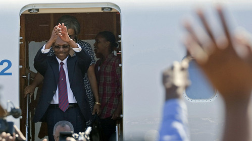 Former Haitian President Jean-Bertrand Aristide gestures to supporters as his wife Mildred and daughter Christine stand behind him at the airport in Port-au-Prince, Haiti, on Friday. He was overthrown by the U.S. in Feb. 2004. by Pan-African News Wire File Photos