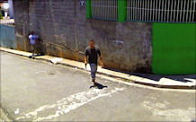 (man with gun facing Google Earth camera)