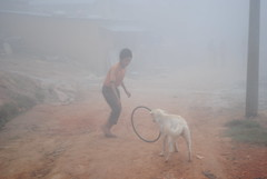 Boy playing with hoop and dog in morning Nepali mist (amazing_tina) Tags: dog mist misty oldschool barefoot 70s morningmist oldschoolgame nepaliboy playinghoop playingmist