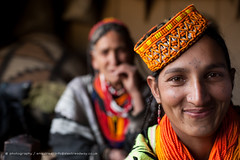 Kalasha women wearing traditional dress (Alex Treadway) Tags: pakistan red orange woman smile hat yellow closeup female happy photography necklace beads costume eyes women asia day pattern native traditional earring culture shell vivid jewellery indoors fabric tribes remote nosering colourful shawl kashmir ornate henna striking relaxed eastern twopeople rare embroidered himalayas impressive indigenous headdress frontview decorated cowrie ethnicminority platted kalasha chitral blurredbackground traveldestination colourimage 5060years rumbur birir 4050years bumboret 2030years northwesternfrontierprovince kalashavalley kalashapeople