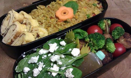 Bento met gebakken rijst met daar bovenop een bloem van wortel en spinazie, ernaast tamagoyaki. In de andere laag gehaktballetjes, kerstomaten, broccoli en spinazie-geitenkaassalade.