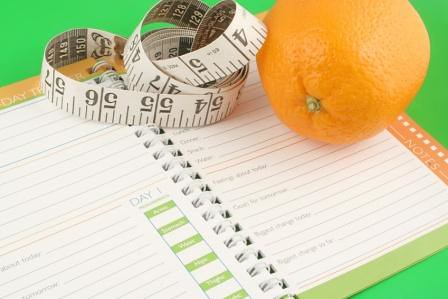 Diet Journal with Measuring Tape and an Orange