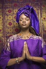 Young African American Woman Praying and Wearing Traditional African Dress (Passive Income Dream.com) Tags: portrait woman black color beautiful fashion vertical female standing scarf person one design clothing colorful pretty pattern quiet dress purple adult serious african prayer religion praying culture style peaceful tranquility tribal calm clothes photograph africanamerican pensive serene meditation spirituality tradition relaxation relaxed cultural traditionaldress headdress twenties traditionalclothing threequarter blankexpression africanculture lookingatviewer religionandmyth