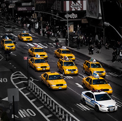 taxis all over and one single police car (pamela ross) Tags: street nyc light shadow people usa ny newyork car yellow america pen 50mm drive driving unitedstates minolta cab taxi police olympus lane timessquare oneway ep1