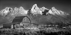 Moulton Barn at Sunrise (Julie Lubick) Tags: ranch old wild bw mountain mountains west building nature beautiful weather architecture barn sunrise fence landscape outdoors us blackwhite nationalpark haze unitedstates outdoor antique pano smoke air rustic scenic nobody panoramic jackson historic western serene homestead wyoming wilderness tetons grandteton landforms rugged imposing steep moulton mormanrow