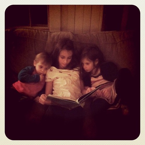Reading to her little sisters