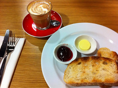 latte coffee in the red cup, with toast, with butter and jam in separate pots, at an airport cafe