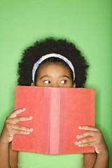 Girl peeking over book. (Passive Income Dream.com) Tags: school portrait color green girl vertical female studio person reading book kid student holding education child looking expression lifestyle indoors photograph learning knowledge africanamerican novel leisure studioshot halflength suspicious preteen bookworm facialexpression covering onepersononly 1012years