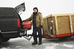 Man going ice fishing. (Passive Income Dream.com) Tags: winter usa lake snow man cold color male men ice weather minnesota horizontal truck season outdoors frozen automobile 4x4 transport adventure greenlake transportation vehicle leisure snowing recreation cooler trailer wintertime tow preparation unpack hitch oneperson icefishing unload fourwheeldrive caucasian sleeting middleaged realpeople 5560years everydayscene