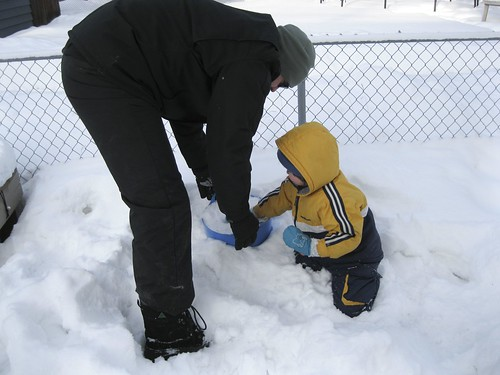 helping daddy fill up a bucket with snow