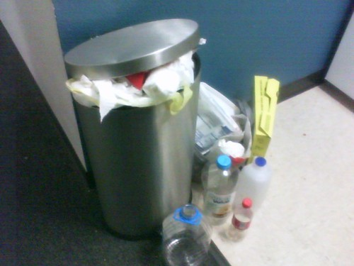 Overflow of trash next to refrigerator in dorm room
