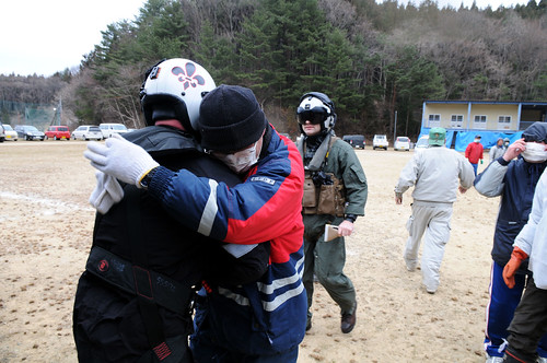 Sailor is embraced by Japanese citizen after delivering supplies.