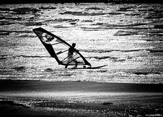Windsurfer on his way to conquer the early spring winds (Michael Wahlgren) Tags: ocean sea blackandwhite bw white black cold canon march is spring sweden surfer surfers winds efs windsurfer varberg windsurfers halland 500d vstkusten 2011 canon500d apelviken 55250mm efs55250mm