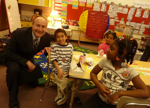 Tim English with three kids – Deputy Regional Administrator Tim English with three students eating breakfast.