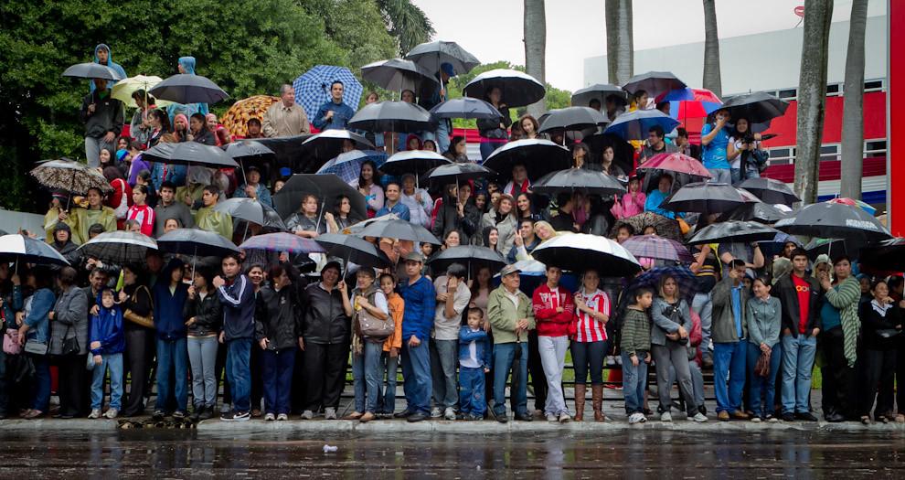 Pese a la intensa lluvia que se registraba en Asunción, mucha gente entre ellos grupos de jóvenes y familias se encontraban aguardando para participar, celebrar y ver el desfile de los Militares sobre la avenida Mariscal López. La fiesta que se vive aún bajo los paraguas. (Tetsu Espósito - Asunción, Paraguay)