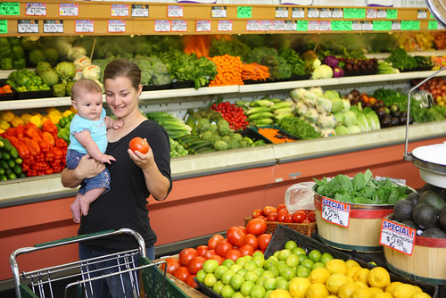 Young mother with baby selects items in produce aisle of grocery store.