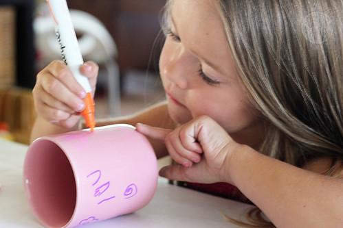 Child painting a cup with a marker