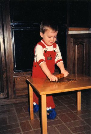 Will (2 1/2), using a child-sized rolling pin to make gingerbread cookies at his toddler table, 1987.