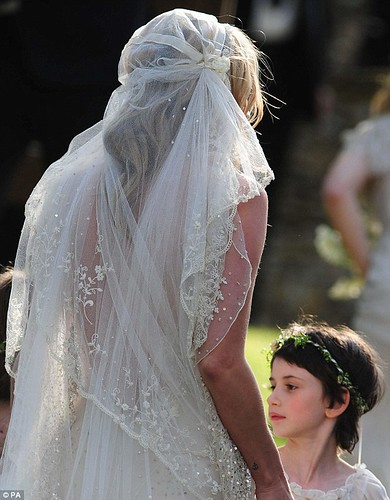 Moss's hair was styled in loose blonde waves underneath the 1920s-style cap veil with flower embroidery on the lace