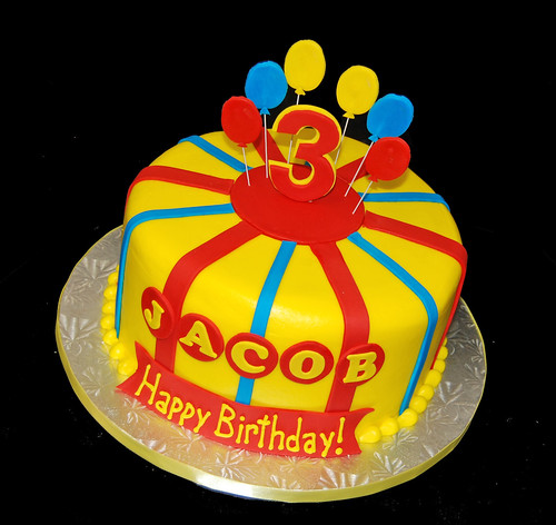 Brightly colored birthday 3rd cake for a Curious George themed party