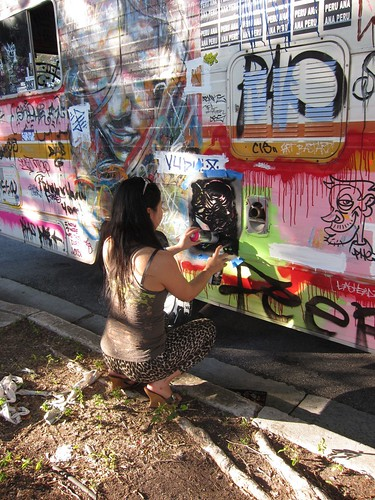 Sugar Junkies. Girl spraying stencil on van.  (Photograph courtesy by Pawn Works)