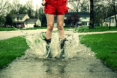 (EyeSeeTheWorld) Tags: street red portrait woman wet water girl grass rain fashion lady female fun puddle outside spring jump play boots walk ripple tint drop neighborhood clothes sidewalk teen teenager shorts dots tone addition spash splish