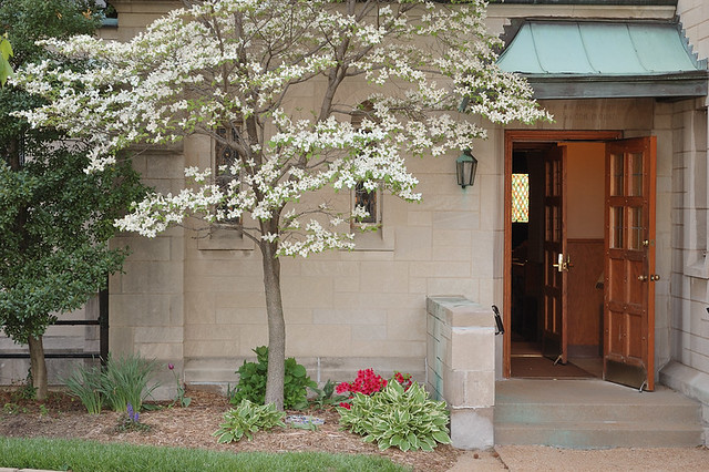 Saint Mary Magdalen Roman Catholic Church, in Brentwood, Missouri, USA - side entrance with spring flowers