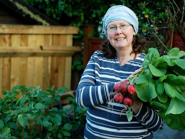 Jane holding a bunch of very large radishes