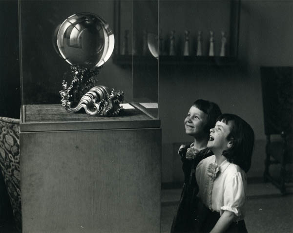 Two girls looking at crystal ball in Harrison Rotunda antechamber. Photo by Reuben Goldberg c. 1950. Penn Museum image 139420.