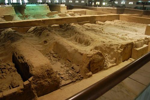Ein noch nicht ausgegrabenens Feld ist zu sehen, um das die Besucher laufen können. In den Gräben sind die Krieger.