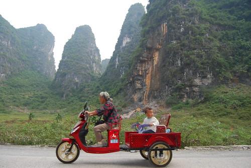 ein rotes motorrad in china mit chinesischer bäuerin und ihrem Enkel auf der Ladefläche vor der Turmkarstlandschaft in China