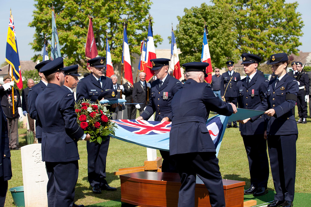 110419 Members of No. 453 Squadron undress the coffin prior to lowering it during Flight Lieutenant Henry 'Lacy' Smith's funeral service at the Ranville War Cemetery, France