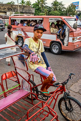Street Portrait - Pedicab Driver (FotoGrazio) Tags: gloves filipinos streetportraiture bicycle pedicabdriver waynesgrazio modesoftransportation passengers sidecab pinoy streetphotography pacificislanders man philippines documentaryphotography feet slippers portrait male streetportrait driver fotograzio waynegrazio job transportation filipino pacificislander jeepney toughjobs business lifeinthephilippines pedicab