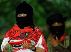 Comandante Ramona wears a black face mask and a white shirt with a red scarf. Only her eyes are visible