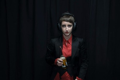 Pale-skinned androgynous person with short brown hair wearing red lipstick, a black blazer over a red shirt and black vest, and headphones. They have a half-full beer bottle in one hand.