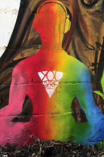 a body sitting crosslegged, wearing headphones, presented in rainbow silhouette -- over the heart is a triangle, pointed down, containing the words, 'You are here'