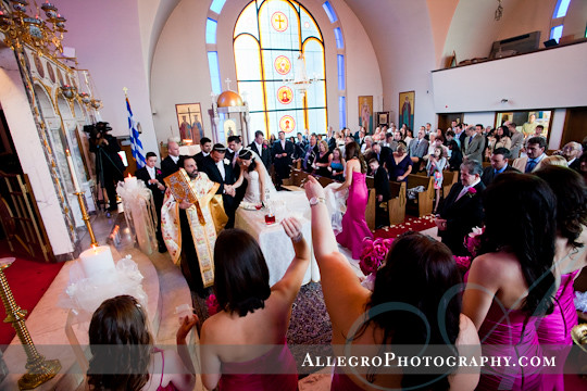 greek-wedding-spring-providence-ri- throwing rice as bride and groom walk around alter in greek orthodox ceremony - pawtucket