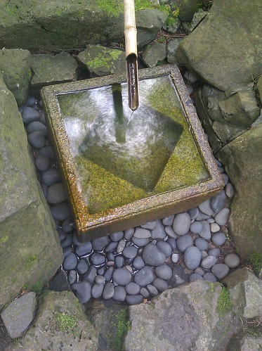 A Square Stone Fountain, fed by a bamboo pipe, its surface reflecting the sky