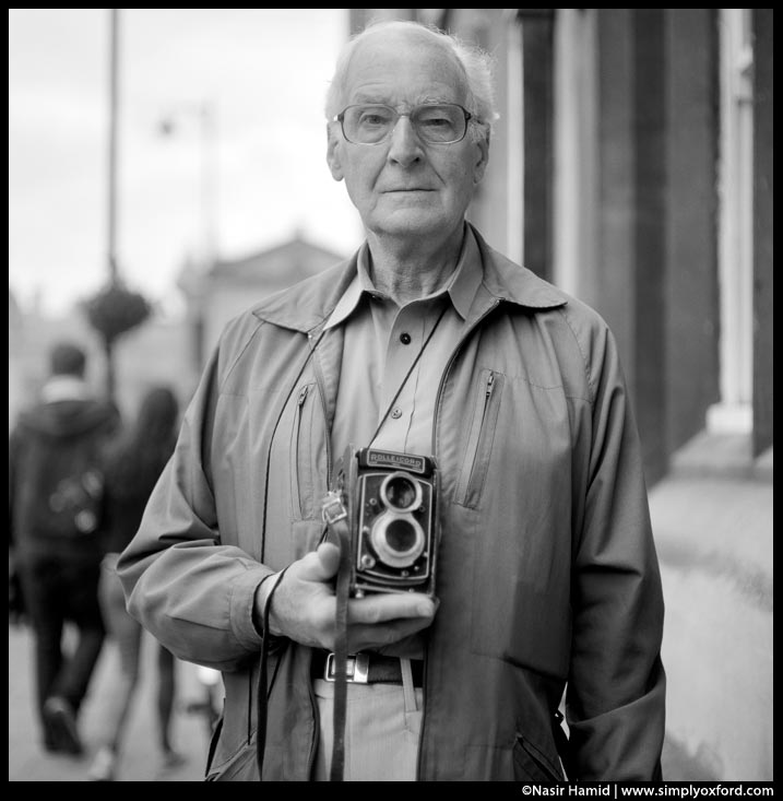 A photographer holding a Rolleicord film camera