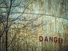 Danger (LornaTaylor) Tags: lornataylor taylorimagesca copyright2009lornataylor danger medal rust rusttextures seatoskyhighway squamish tree winter lornataylorphotography oiltank environment texture