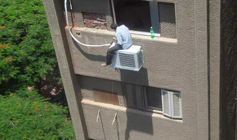 man sat on aircon on a tall building