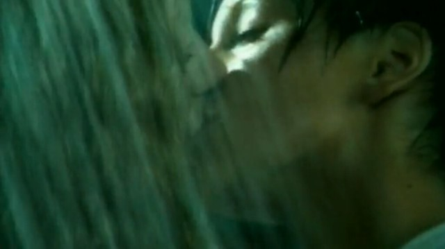 Image is a close up of Lena Katina and Yulia Volkova engaged in a kiss in the rain, taken from t.A.T.u's