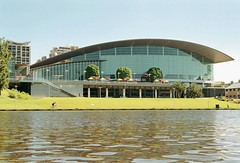 Adelaide Convention Centre from the River Torrens (looking south-southwest) (Adriano_of_Adelaide) Tags: city reflection building water grass sunshine cyclist sunny bluesky conventioncenter adelaide cbd ripples riverbank modernarchitecture clearsky sunnyday modernbuilding centralbusinessdistrict conventioncentre calmwater contemporaryarchitecture ripplingwater rivertorrens adelaideconventioncentre cloudlesssky torrensriver glassfacade cityofadelaide contemporarybuilding riversidebuilding rivertorrensprecinct riverbankprecinct