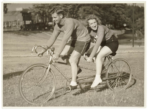 Oppy (Hubert Opperman) and woman, possibly Edna Sayers, on tandem bicycle, by Sam Hood