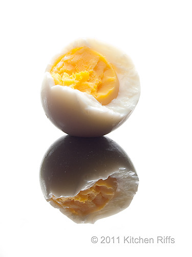 hard-boiled egg with bite eaten on black acrylic